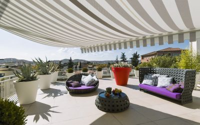 exteriors shots of a modern terrace with awnings and wicker sofa
